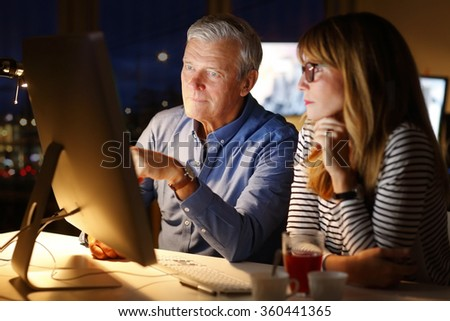 Portrait of professional business team working late at office. Senior businessman and middle age assistant sitting in front of computer and consulting. - stock photo