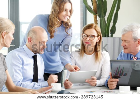 Portrait of professional financial team sitting at office and analyzing business plan. Business group working on financial plan while using digital tablets and personal computer.