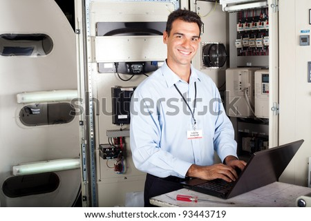 portrait of professional industrial technician in front of machinery - stock photo