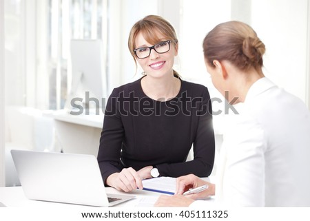 Portrait of professional investment advisor woman sitting at her workplace in front of laptop and consulting with businesswoman. - stock photo