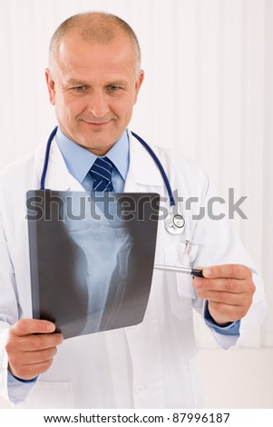 Portrait of professional male doctor look down and point x-ray