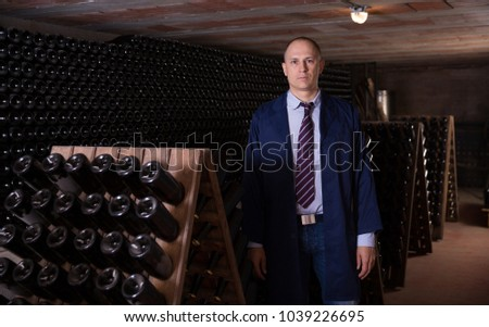 Portrait of professional male winemaker standing in wine cellar