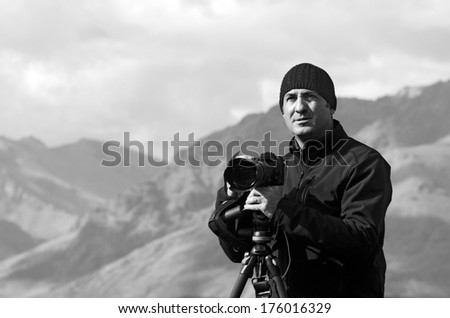 Portrait of professional on location and nature photographer (man) during work outdoor. (BW) - stock photo
