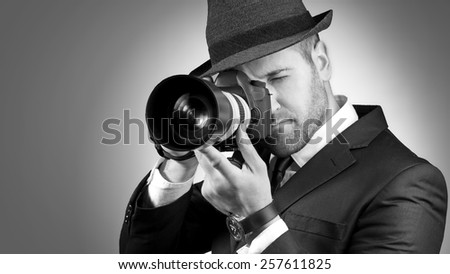 Portrait of professional photographer in action. Black and white - stock photo