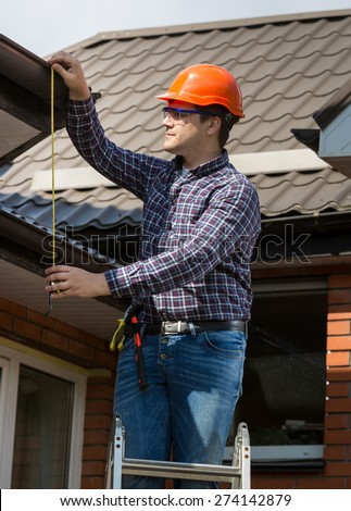 Portrait of professional worker measuring height of roof with tape - stock photo