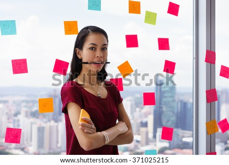 Portrait of proud assistant with pen in mouth. The mixed race woman stands in modern office against a window full of adhesive notes with tasks - stock photo
