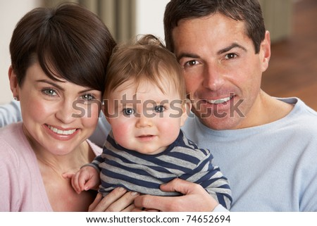 Portrait Of Proud Parents With Baby Son At Home - stock photo