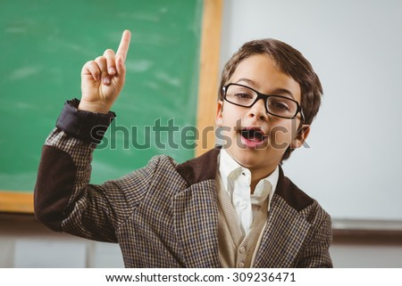 Portrait of pupil dressed up as teacher having an idea in front of chalkboard - stock photo