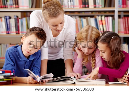 Portrait of pupils and teacher reading interesting book in library
