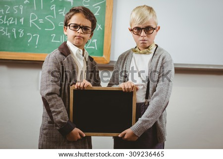 Portrait of pupils dressed up as teachers holding chalkboard in a classroom - stock photo