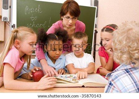 Portrait of pupils looking at open book during lesson with attention