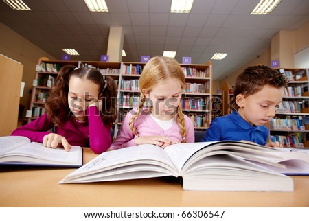 Portrait of pupils looking at pages of textbooks at reading lesson - stock photo