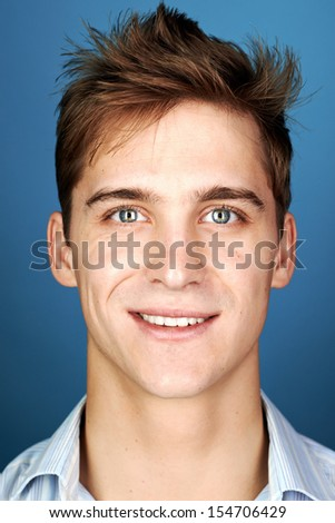 Portrait of real happy smiling man, natural on blue background - stock photo