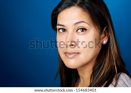 portrait of real woman face headshot on blue background - stock photo