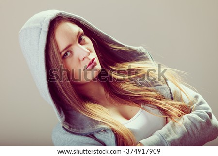 Portrait of rebellious pensive thoughtful teenager crossing arms wearing hooded sweatshirt. - stock photo