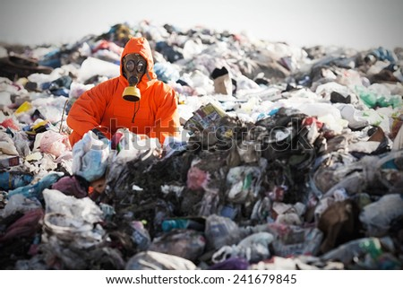 Portrait of recycling worker among garbage bags on the landfill - stock photo