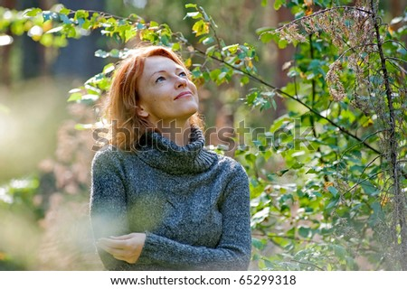 Portrait of red-haired adult woman in nature - stock photo