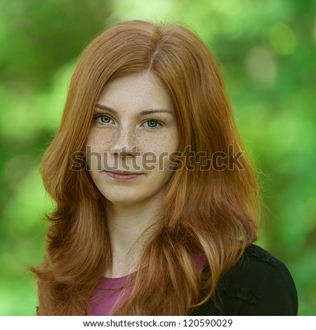 Portrait of red-haired beautiful young woman, against green of summer park. - stock photo