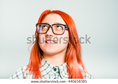portrait of red-haired girl have a good idea, glasses, isolated on a gray background