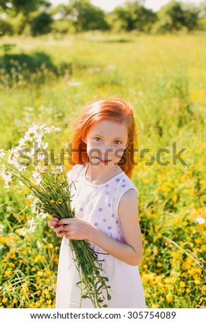 Portrait of red-haired girl holding flowers in a beautiful field