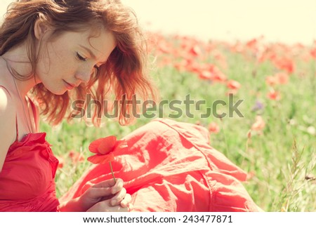 Portrait of red-haired girl in a wonderful summer field - stock photo