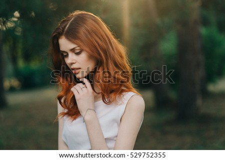 Portrait of red-haired girl in the park in the last rays.