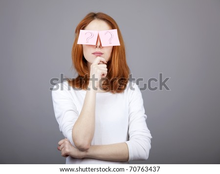 Portrait of red-haired girl with colorful funny stickers on eyes. Studio shot. - stock photo