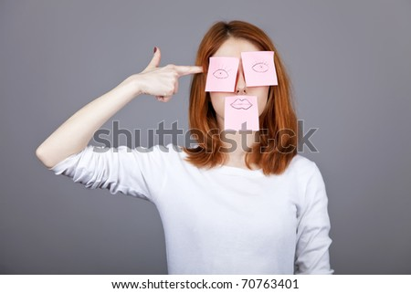 Portrait of red-haired girl with colorful funny stickers on mouth and eyes. Studio shot. - stock photo