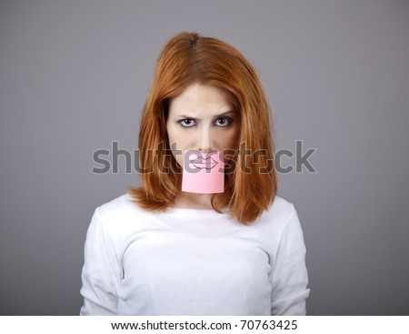 Portrait of red-haired girl with colorful funny stickers on mouth. Studio shot. - stock photo