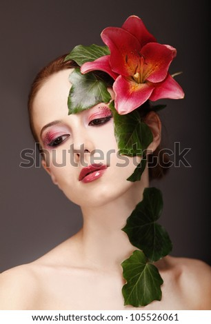 Portrait of red-haired girl with flower and make-up. Studio shot.