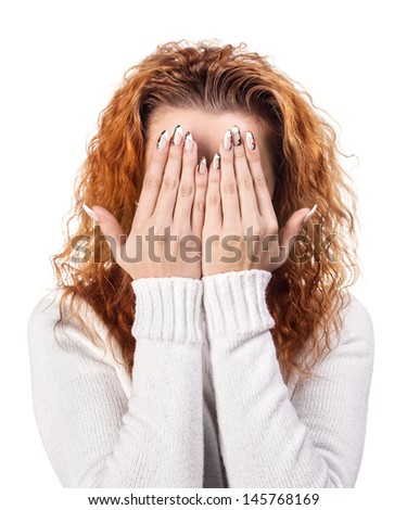 Portrait of red-haired woman covering her face by the hands, over white background