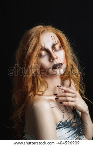 Portrait of red-haired woman with eyes closed and make up against of black background