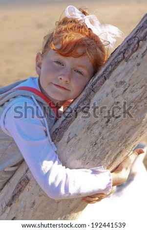 portrait of red headed girl at the beach with her arms around a driftwood log  - stock photo