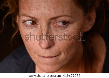 Portrait of redhead woman anxiety expression with tears in eyes trying not to cry suppressed emotion - stock photo