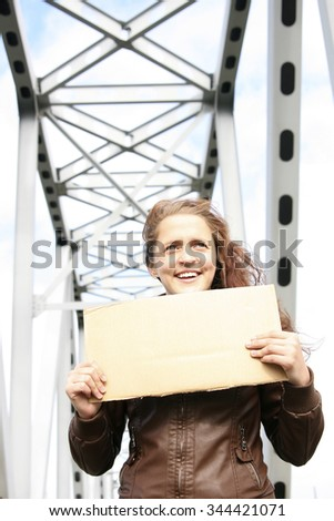 portrait of redhead woman holding paper sheet. Attractive curly keep in hands empty card board with copy space standing on road under metal bridge against blue sky with clouds