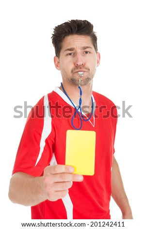 Portrait of referee blowing whistle while showing yellow card over white background - stock photo