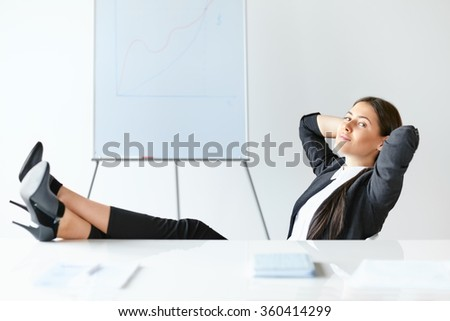 Portrait of relaxed business woman sitting with legs on desk in the office