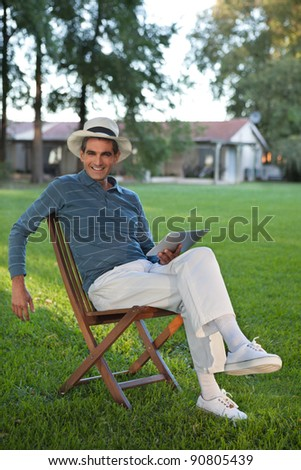Portrait of relaxed casual man sitting in park holding tablet PC