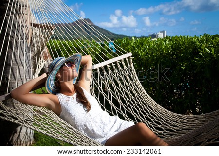Portrait of relaxed gorgeous young woman lying in hammock on a tropical island. Peace of mind, Hawaii, Oahu - stock photo