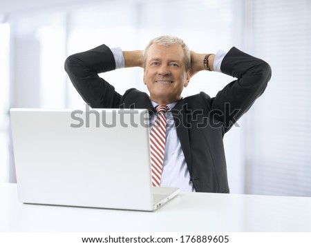 Portrait of relaxed senior businessman sitting in office. He wears shirt and tie. - stock photo
