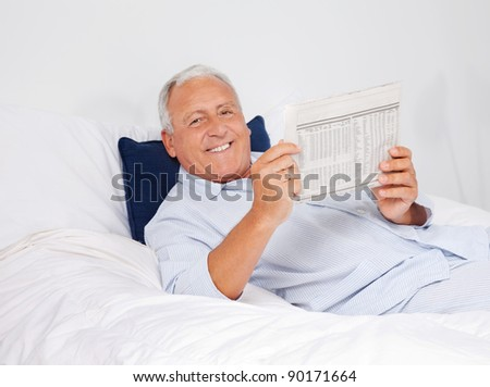Portrait of relaxed senior man reading newspaper while lying on bed at home - stock photo