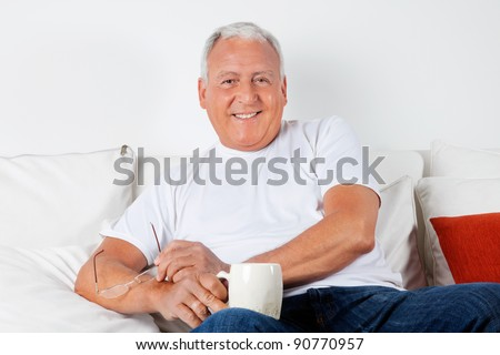 Portrait of relaxed senior man sitting on sofa with warm drink - stock photo
