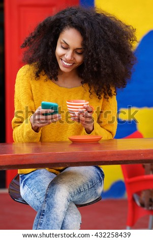 Portrait of relaxed young african american woman reading text message on mobile phone at coffee shop - stock photo