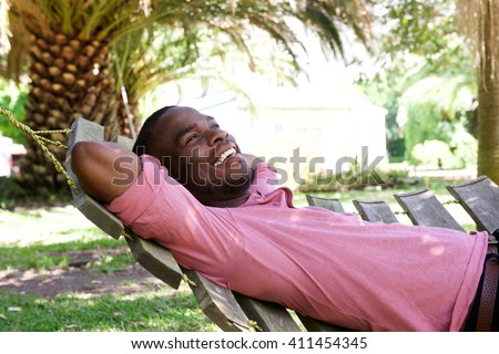 Portrait of relaxed young african man lying outdoors on a hammock - stock photo
