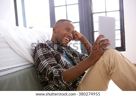Portrait of relaxed young afro american guy sitting and using digital tablet at home - stock photo