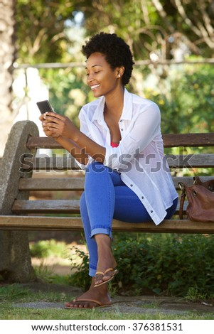 Portrait of relaxed young lady sitting on a park bench and reading a text message on her mobile phone - stock photo