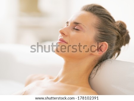 Portrait of relaxed young woman in bathtub - stock photo