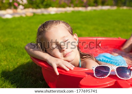 Portrait of relaxing adorable little girl enjoying her vacation in small pool outdoor - stock photo