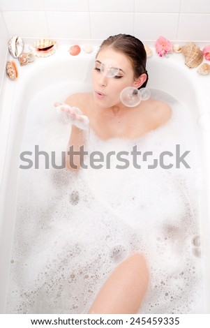 portrait of relaxing beautiful young lady lying in a spa bath blowing soap bubbles  - stock photo