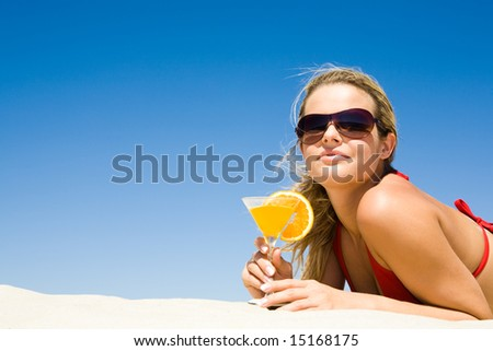 Portrait of relaxing woman wearing sunglasses with glass of cocktail in hand lying on sand - stock photo